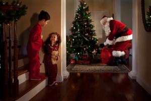 Two children sneak downstairs to get a glimpse of Santa Claus on Christmas Eve.